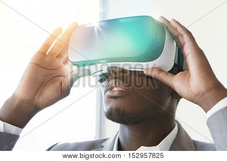Technology And Entertainment. African Employee Dressed In Suit, Experiencing Virtual Reality, Wearin