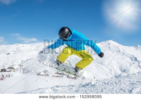 Young snowboarder in protective gear jumping when sliding down the hill at the ski resort