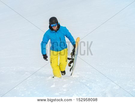 Happy sportive young man holding snowboard in his hands and moving up the hill