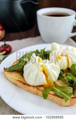 Boiled eggs in a pouch (poached) on toast and crisp green leaves of arugula and a cup of tea. Dietary breakfast.