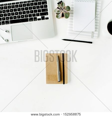 Flat lay home office workspace with laptop diary coffee succulent and headphones on white background.