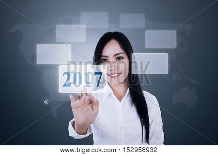 Portrait of a young Asian businesswoman pressing virtual numbers 2017 on the futuristic interface