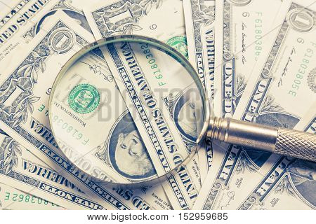 Finance concept. Gold magnifying glass on dollar banknotes.