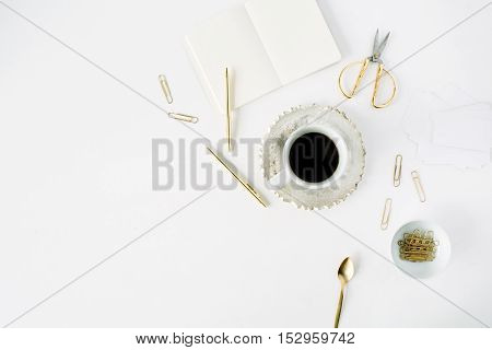 coffee cup empty diary and golden accessories: tea spoon pen clips and scissors on white background. flat lay top view