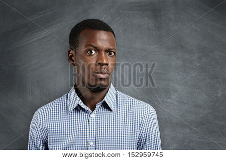 Human Face Expressions And Emotions. Close Up Shot Of Doubtful African Man Dressed Casually Looking
