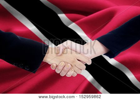 Portrait of Two business handshaking after ending discussion with Trinidad and Tobago flag