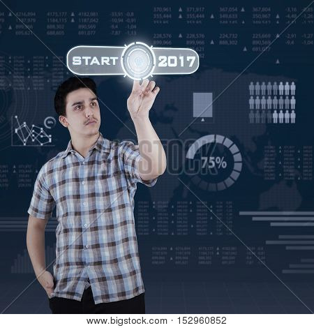 Picture of Caucasian businessman pressing a start button with numbers 2017 and financial statistic background on the virtual screen