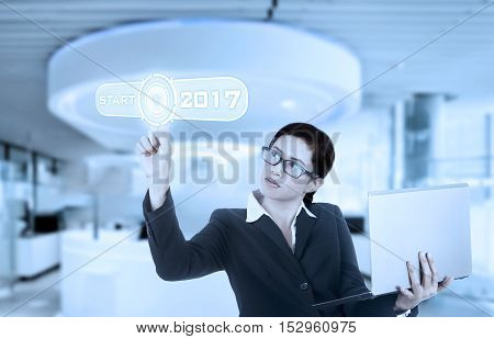Young Asian businesswoman touches a start button with numbers 2017 on the virtual screen in the office