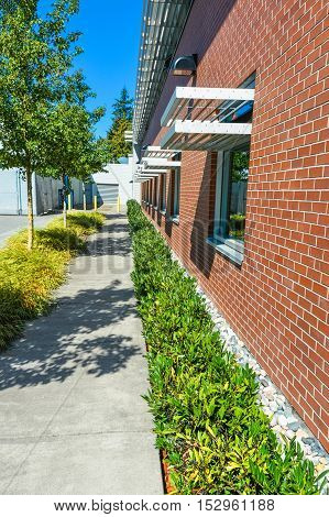 Brick wall of office building with weather shields above the windows. Office building with small hedge and concrete pathway along the wall