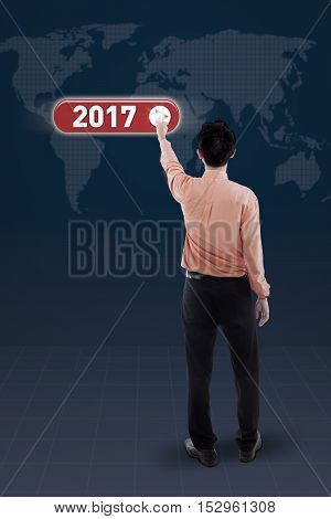 Rear view of a male entrepreneur pressing a virtual button with numbers 2017 and world map on the futuristic screen