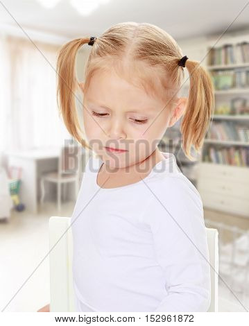 The concept of family happiness, and preschool education of the child , against a child's room with bookshelves.Distressed small, blonde girl with white t-shirts without a pattern.