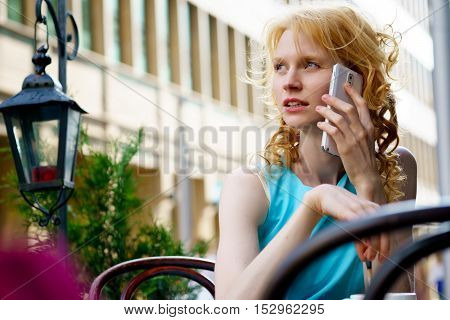 Outdoors portrait of smiling young woman in blue summer dress talking on mobile in cafe