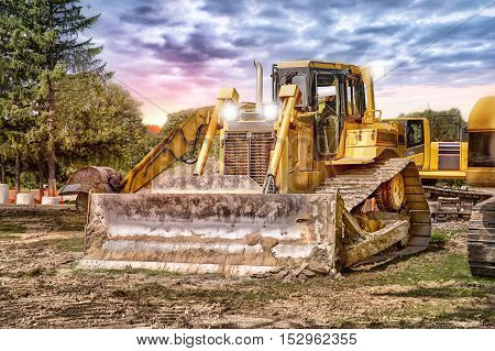 Large bulldozer at construction site sunset in background.