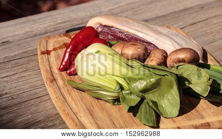 Natural raw duck breast with organic portabella mushrooms, red jalapeno pepper, green Chinese bok choy, green onion and ginger on a cutting board on a rustic wood farm table before going into duck pho soup.