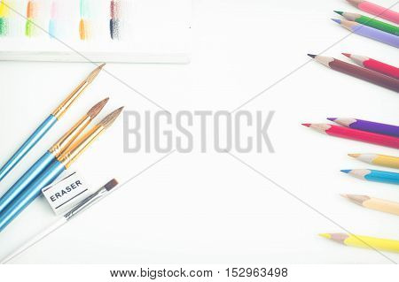 Top view of art supplies on white table. Colored pencils, paintbrushes and sketchbook.  May be used as product mockup.