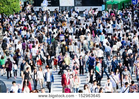 Blurred photo of Pedestrians crossing the busiest crosswalk in the world in the Shibuya district in Tokyo, Japan