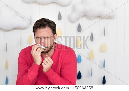 Bad cold. Pleasant moody ill man sneezing and wiping his nose with a paper tissue while standing against the wall