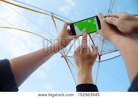 Man and woman in bivouac with transparent gauze dome and blue cloudy sky above looking at map on smartphone holded in hands
