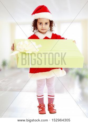 Cute little girl in a coat and hat of Santa Claus, holding a big green box , tied with a bow.In the room with a big bright window.