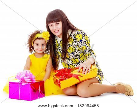 Beautiful young mother and her adorable little daughter , sitting surrounded by Christmas gifts.Isolated on white background.