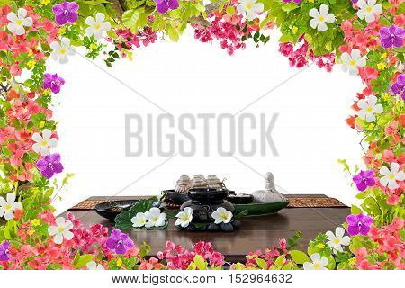 Thai spa massage setting herbal compress balls essential oil bottle frangipani and incense on beautiful orchid flower and leaves frame