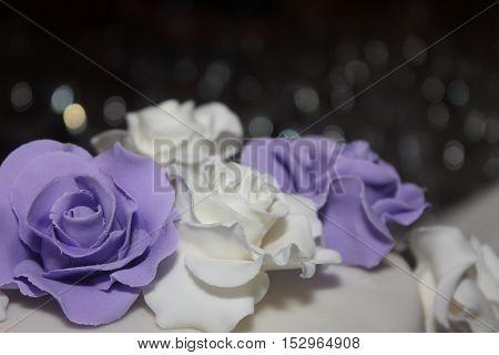 White and purple wedding cake decor roses.