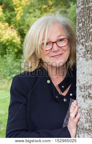 Side View Of A Mature Woman Leaning Against Tree Trunk