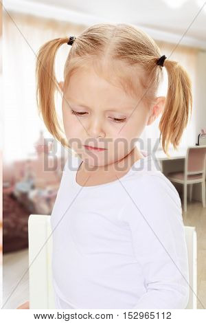 Beautiful little blonde girl with pigtails on his head, white t-shirts without a pattern. The girl is upset about something. Close-up.