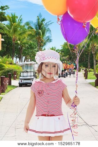 Adorable little girl in short summer dress and white Panama hat on his head. Girl holding bunch of colorful balloons.Close-up.On the background of the track