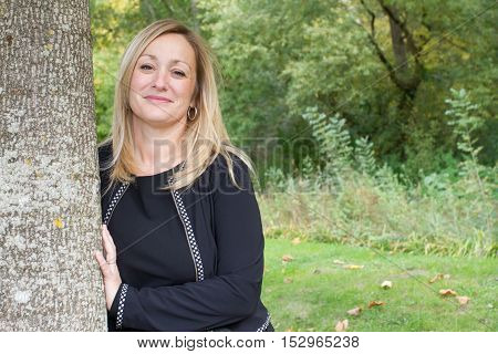 a Confident woman leaning against tree trunk