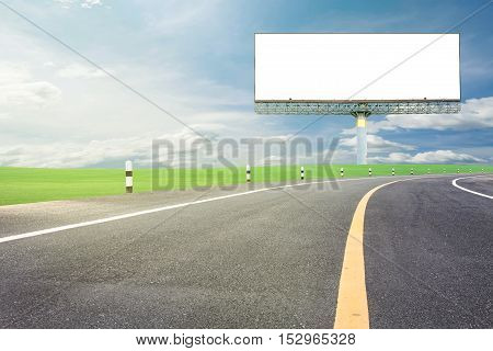 Blank billboard for your advertisement with space for text on road curvewith green grass and blue sky background