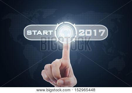 Image of hand pressing a virtual start button with numbers 2017 and world map background on the futuristic screen