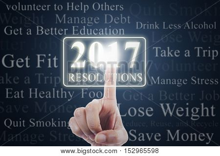 Image of hand pressing a virtual button with numbers 2017 and new year resolutions