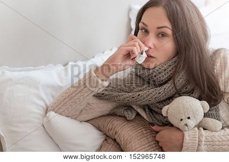 Seasonal epidemics. Gloomy depressed ill woman hugging a stuffed toy and holding a paper tissue while lying on the bed