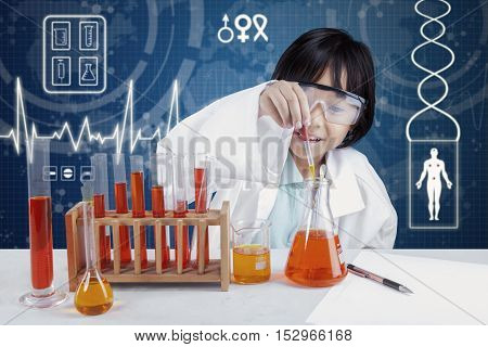 Picture of a little scientist using chemical liquid to make science research in the laboratory