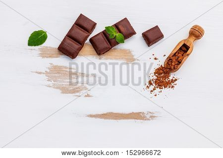 Pieces Of Chocolate With Mint On White Wooden Background