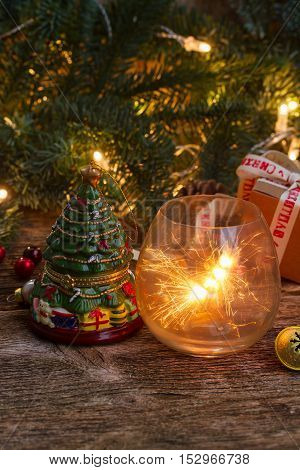Christmas magic glowing light with evergreen tree on wooden background, low key