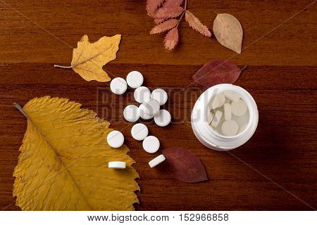 Heap of round white pills and pill bottle on yellow leaves
