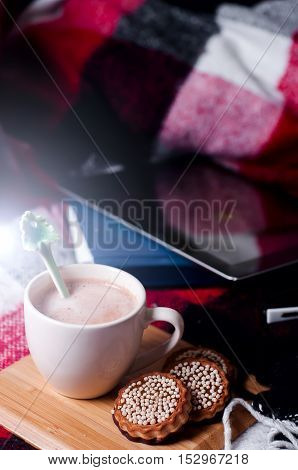 Tablet PC and cup of hot cocoa on a bed with a blanket.