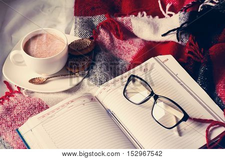Cup of cocoa staying on open book and glases on the bed with blanket, Good morning.