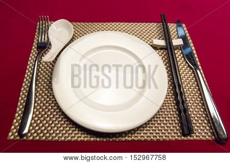 Tableware consisted of white ceramic dish fork chopsticks knife and golden pad put on red table