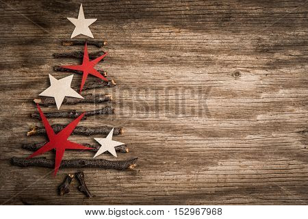 Branches with white and red stars in a shape of christmas tree and copy space