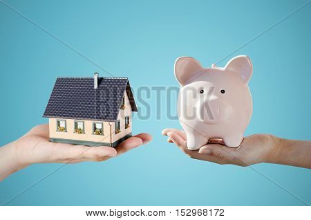 Hand Holding House Miniature And Piggy Bank. Home Finance Concept