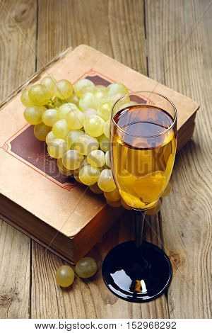 Ripe grapes old book and glass of wine on a wooden table