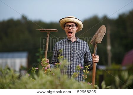 Funny expressive portrait of farmer man with shovel and rake with open-mouthed
