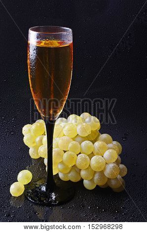 Grapes and wine glass with water drops on black background