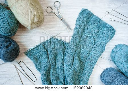 Knitted blue cloth and skeins of wool on the wooden table
