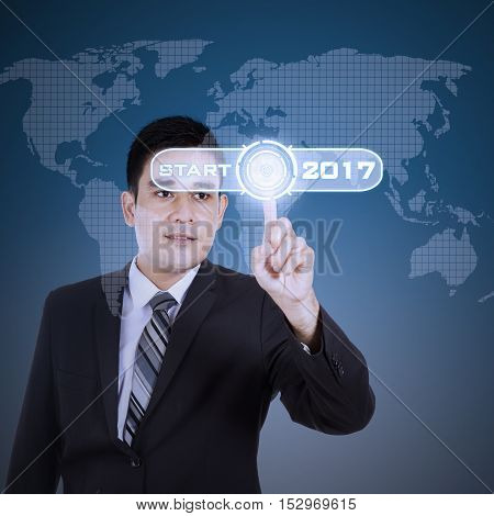 Portrait of a young businessman pressing a virtual start button with numbers 2017 and world map on the futuristic screen