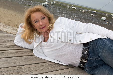 Lovely Blond Woman Laying On The Wooden Jetty