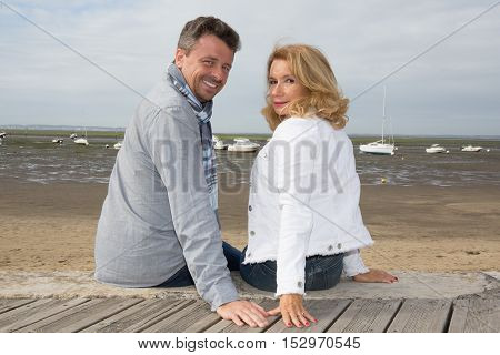 Couple Sitting On Wooden Jetty And Looking At Camera